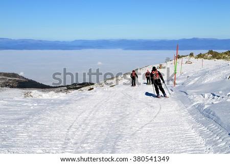 Three skiers descend from the peak, Cherni Vrah, Vitosha Mountain, Bulgaria - stock photo