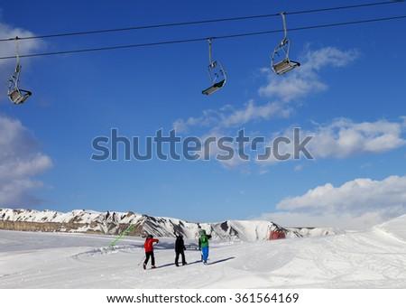 Three skiers on slope at sun nice day. Greater Caucasus, Mount Shahdagh. Qusar rayon of Azerbaijan. - stock photo