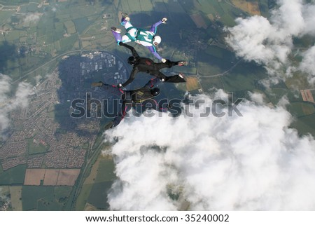 Three skydivers doing formations - stock photo