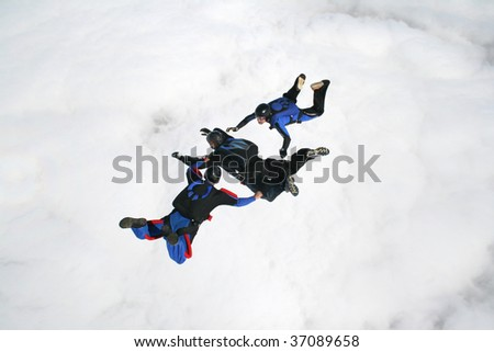 Three skydivers in freefall with a bank of clouds beneath them - stock photo