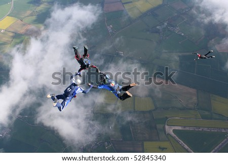 Three skydivers in freefall with a fourth one below them - stock photo