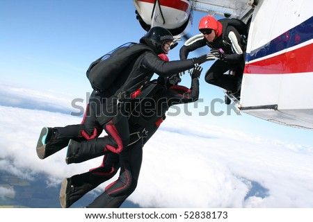 Three skydivers jump from a plane - stock photo