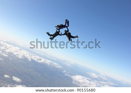 Three skydivers just after exiting an airplane - stock photo