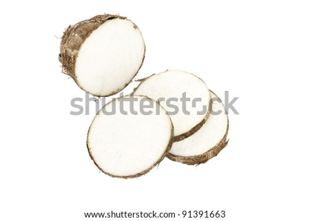 Three slices of Malanga root laying next to the remaining piece - stock photo