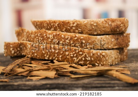 three slices of whole bread with sesame seeds on wooden table - stock photo