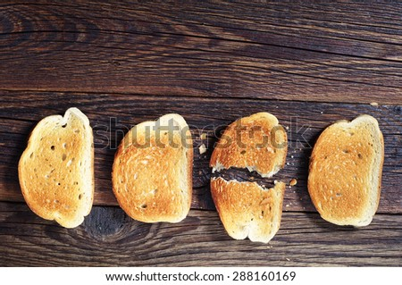 Three slices toasted bread and one ripped on dark wooden background, top view - stock photo
