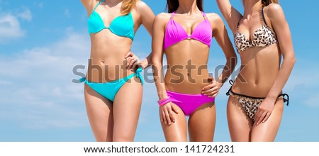 Three slim young girls in bikinis on the beach - stock photo