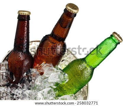 Three small beer bottles in a bucket with ice close up, top view - stock photo