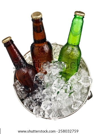 Three small beer bottles in a bucket with ice, top view - stock photo