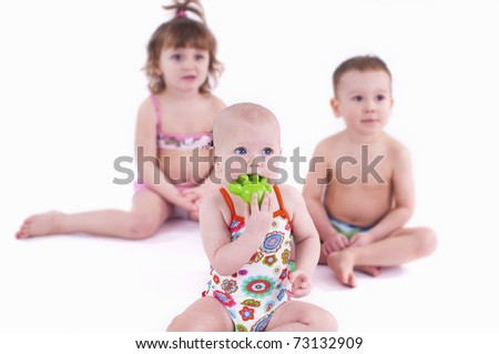Three small children in swimsuit play with toys. Two girls and one boy sitting on a white background.