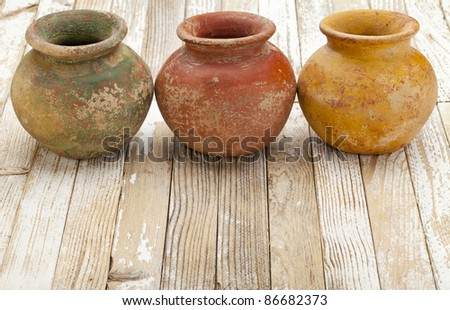 three small  clay plant pots (mass produced planter) with rough, grunge finish,  on white rustic wood background - stock photo