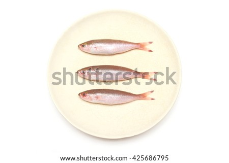 three small fresh fish prepared for cook lay down on dish or plate - stock photo