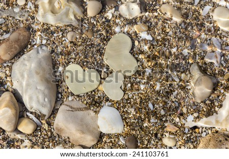 Three small metallic heart shapes are placed in shallow water with seashells and sand. The water ripples. - stock photo