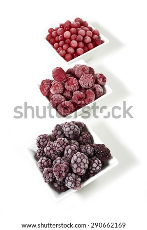 Three small porcelain dishes with frozen raspberries, currants and blackberries on white background