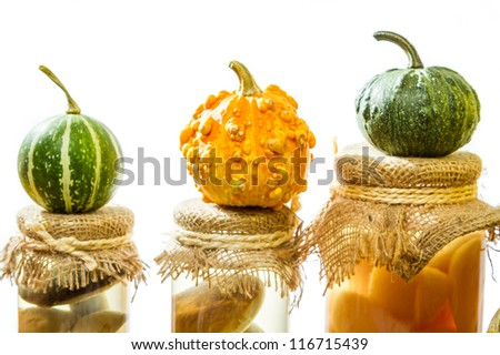 Three small pumpkins on jars in the basement - stock photo