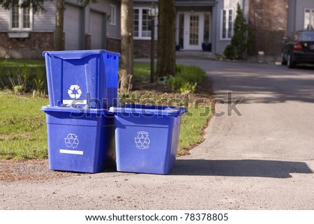 Three small recycle bins on curb - stock photo