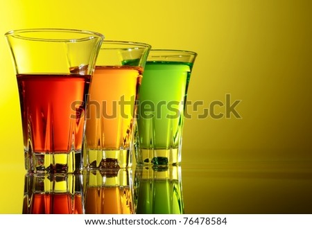 Three small shot glasses of alcoholic beverages - stock photo