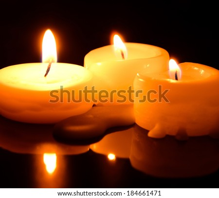 three small tea lights in the dark - stock photo