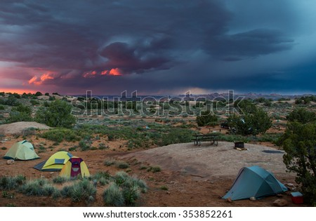 three small tents in a desert landscape with a dramatic pink and blue thunderstorm sky and arches national park in background - stock photo