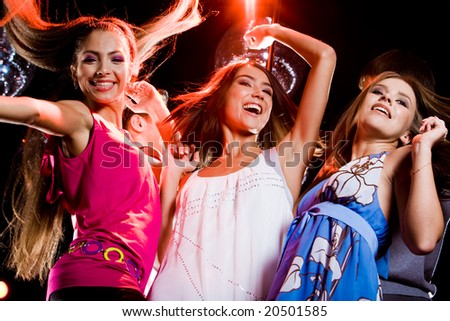 Three smart dancers moving at disco while raising their arms - stock photo