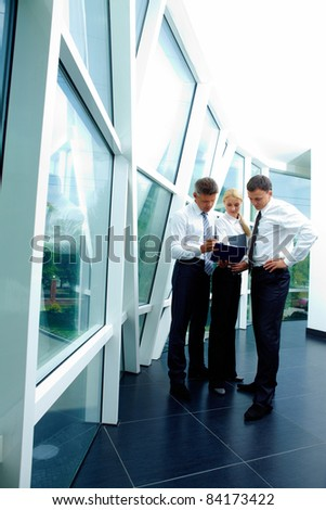Three smart employees discussing plan at meeting - stock photo