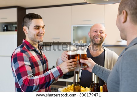 Three smiling adult male friends with glasses of beer and chips at the kitchen