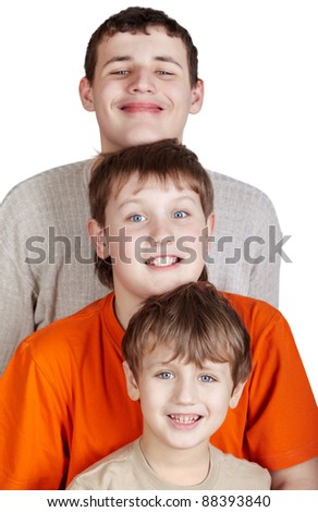 Three smiling boys stand one after another and putting own head on a head standing ahead, focus on small boy