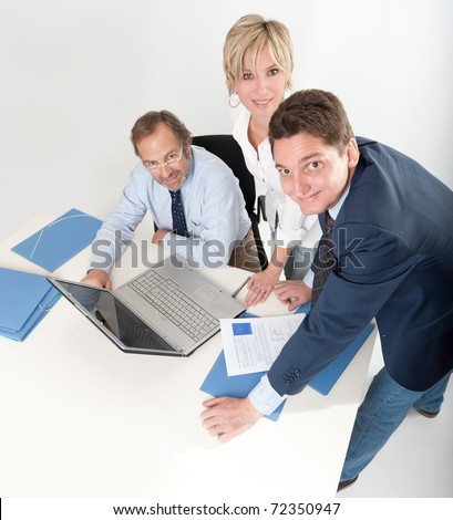Three smiling business people looking at the camera - stock photo