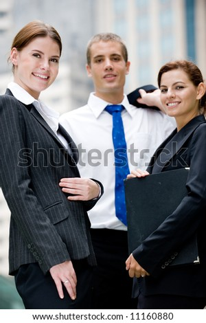 Three smiling business people standing outside in city - stock photo