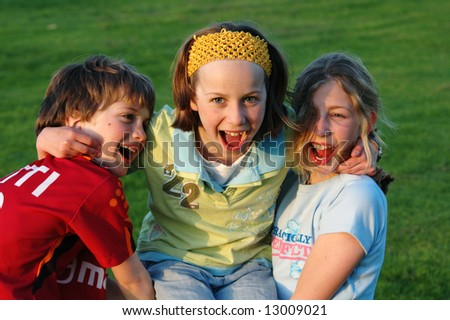 three smiling children at the park - stock photo
