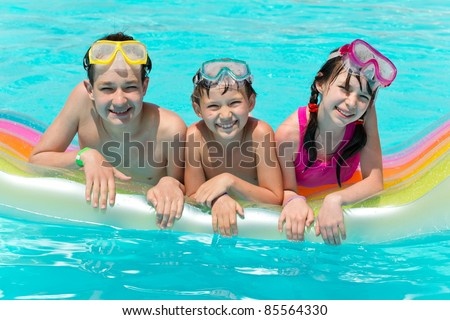 Three Smiling Children in Pool - stock photo