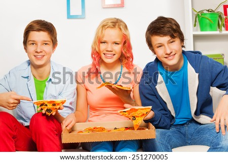 Three smiling friends hold pizza pieces and eat - stock photo
