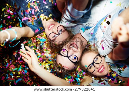Three smiling friends making selfie while lying on the floor in nightclub - stock photo