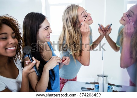 Three smiling friends putting makeup on together in the bathroom - stock photo