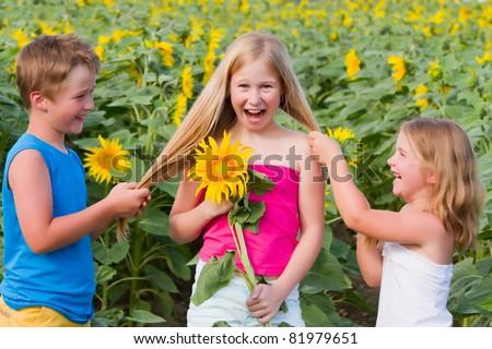 three smiling happy children in sunflowers field - stock photo