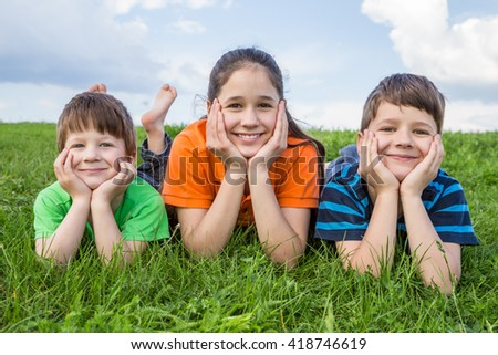 Three smiling kids lying together on green grass meadow