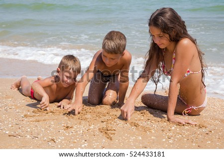 Three smiling kids on the beach playing on the sand near water