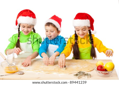 Three smiling kids with Christmas cooking, isolated on white - stock photo