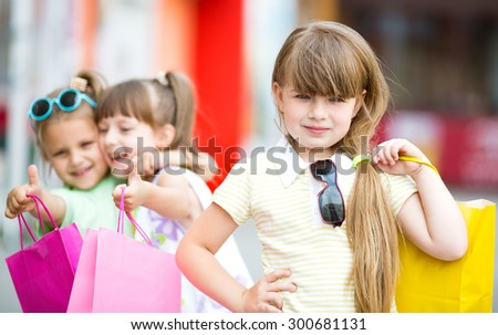 three smiling little girls with shopping bags walking in the city - stock photo