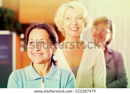 three smiling mature women posing at home interior