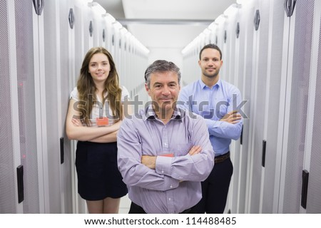 Three smiling people standing in data center with arms crossed - stock photo