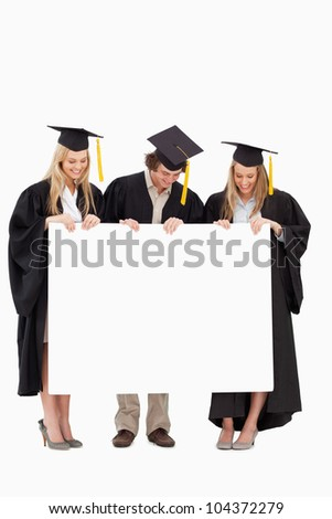 Three smiling students in graduate robe holding a blank sign against white background - stock photo