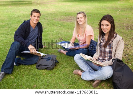 Three smiling students studying together in a park - stock photo
