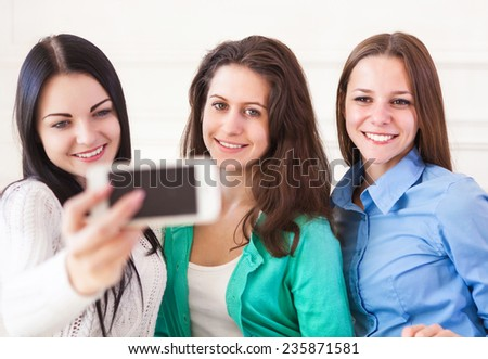 Three smiling teenage girls taking selfie with smartphone camera at home. Friendship, technology and internet concept