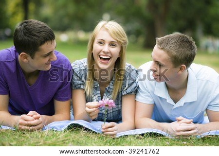 Three Smiling Teens Lying on a Blanket in a Park - stock photo
