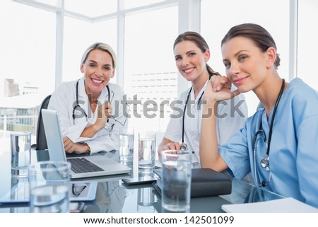 Three smiling women doctors looking at the camera - stock photo