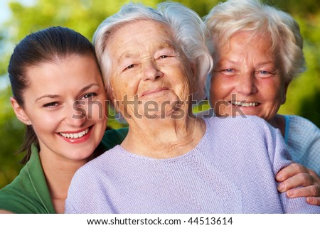 Three smiling women: mother, her daughter and granddaughter - stock photo