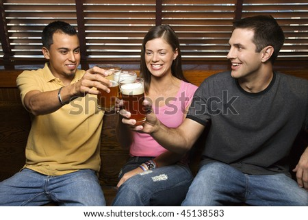 Three smiling young adult friends sitting on a bench toasting with their beers. Horizontal shot.