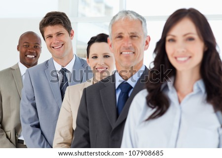 Three smiling young business people in the background following their leaders - stock photo