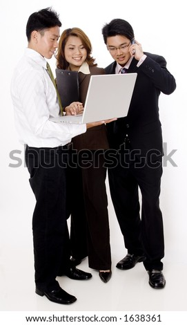 Three smiling young business people looking at a laptop computer - stock photo